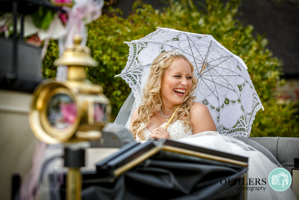 Happy Bride in an open top carriage laughing under an umbrella shielding herself from the sun.