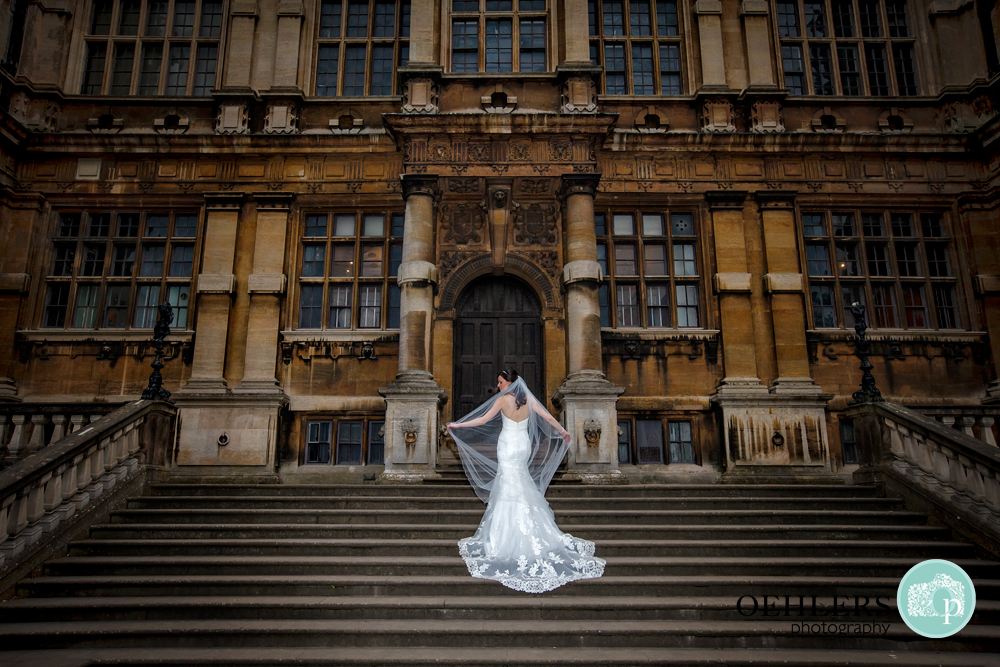 Bride displaying the back of her dress and veil on the front steps of Wollaton Hall