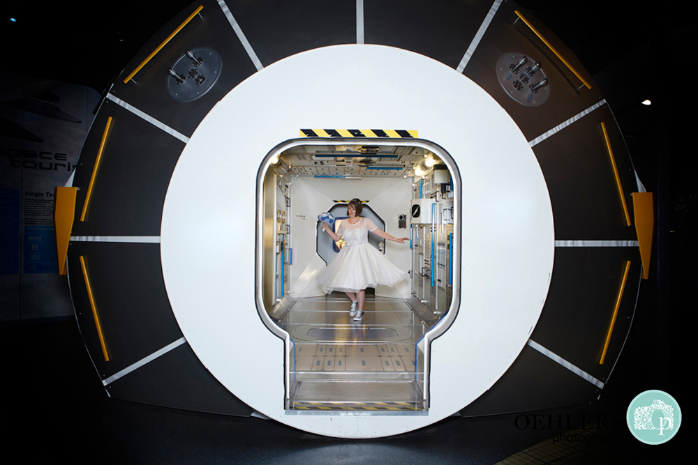 Bride dancing inside a space capsule in The Space Centre in Leicester