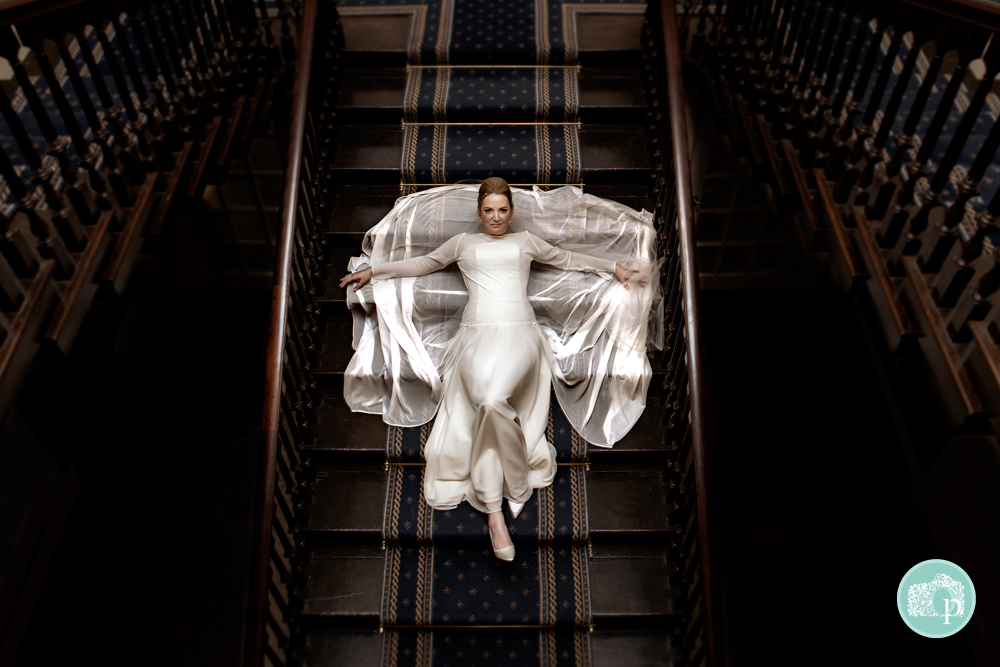 Bride lying back on a staircase. Photograph is taken from above.