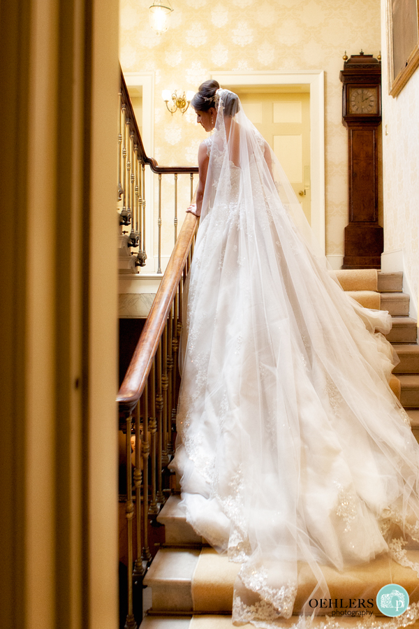 Bride leaning against a staircase