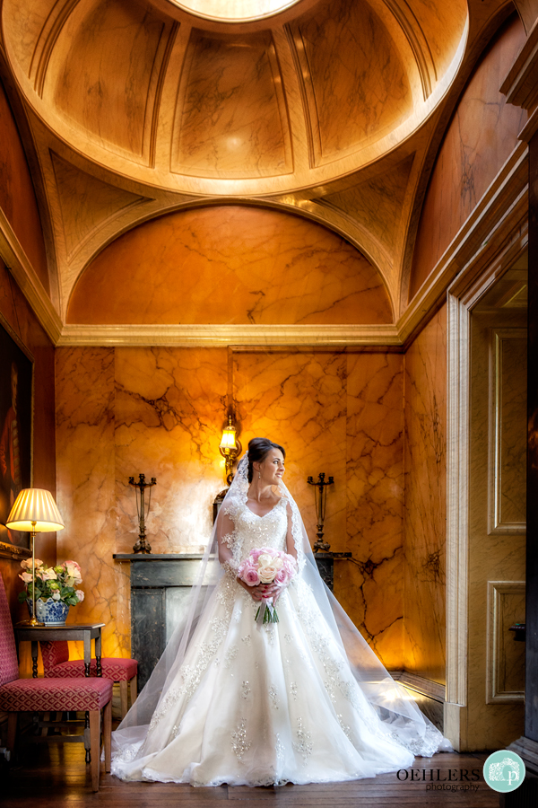 Bride in beautiful indoor surroundings looking to her left through a door