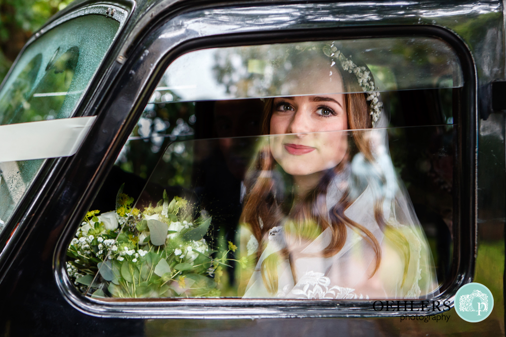 Bride looking through the wedding car window at the camera.