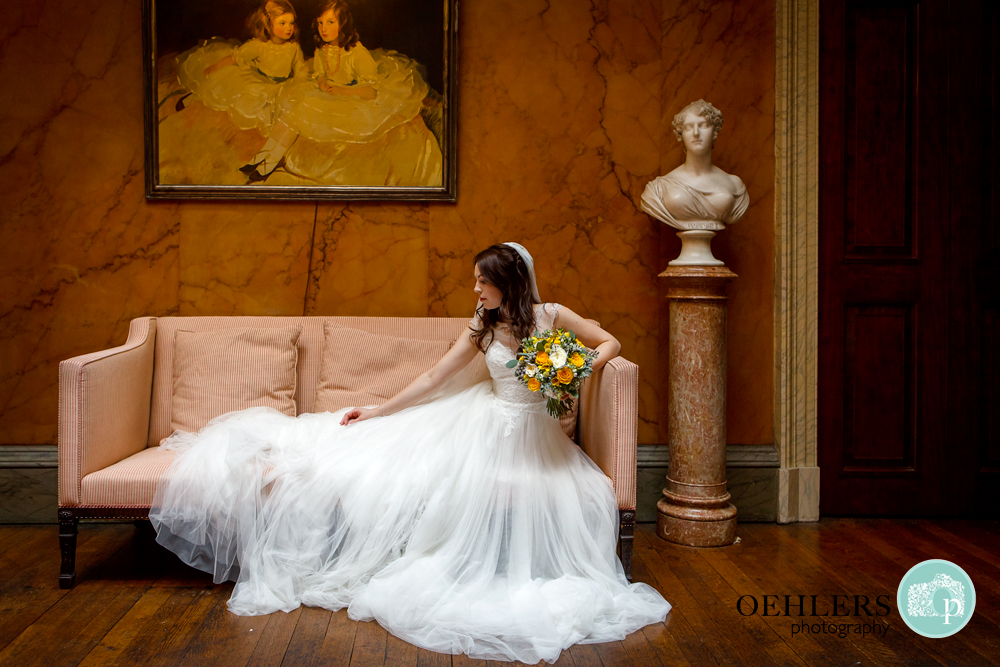 Bride sitting on a sofa adjusting the train of her dress.