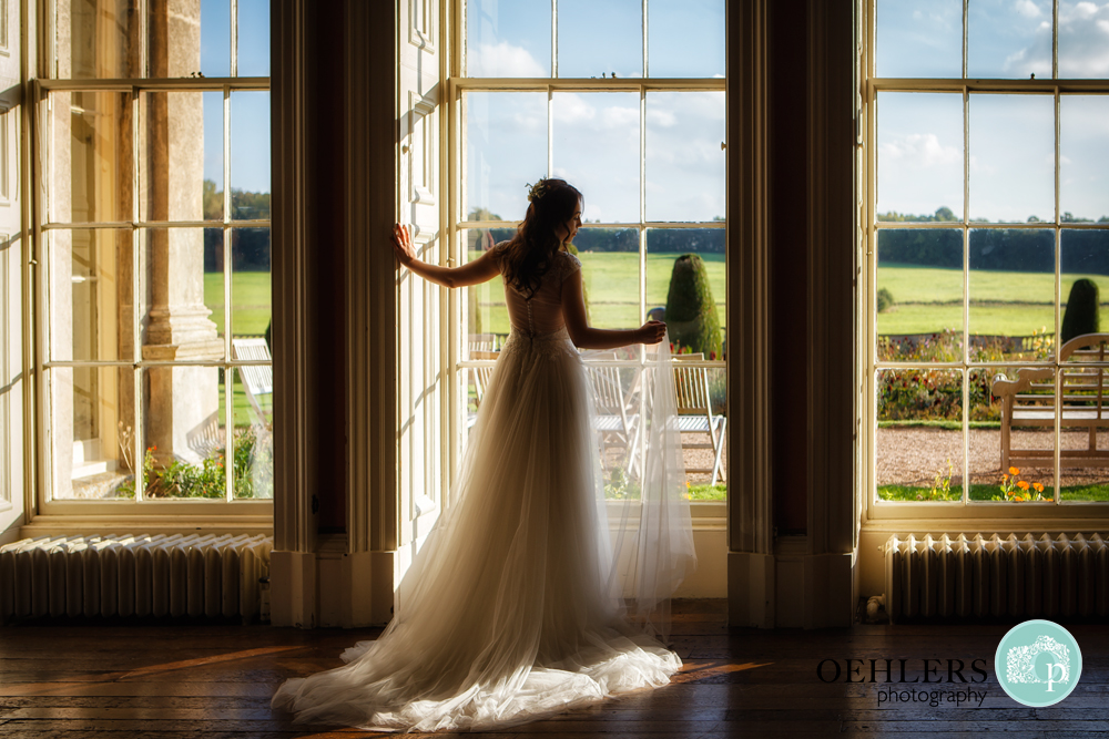 Silhouette of a bride posing against a floor to ceiling window.