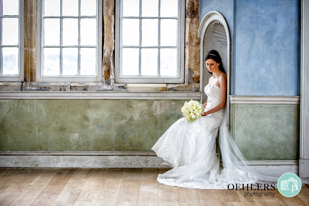 Bride in an archway sitting down looking at her flowers in pastel blue and green background.
