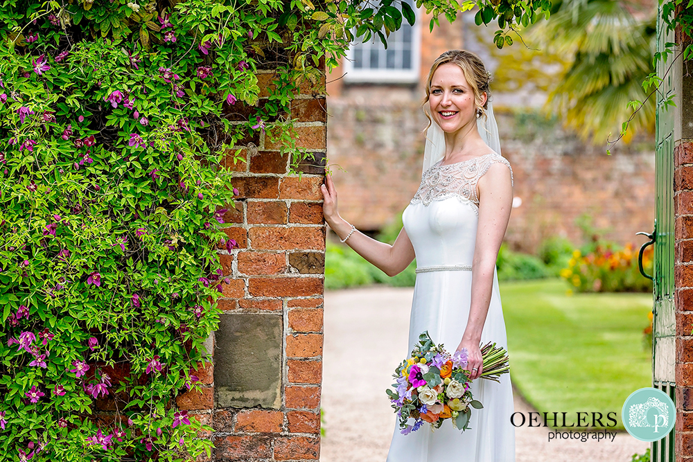 Bride  standing in an archway in the Gardens of Calke Abbey looking directly into the camera.