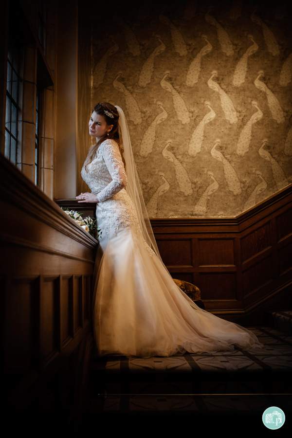 Bride leaning against a windowsill on the staircase looking out of the window.