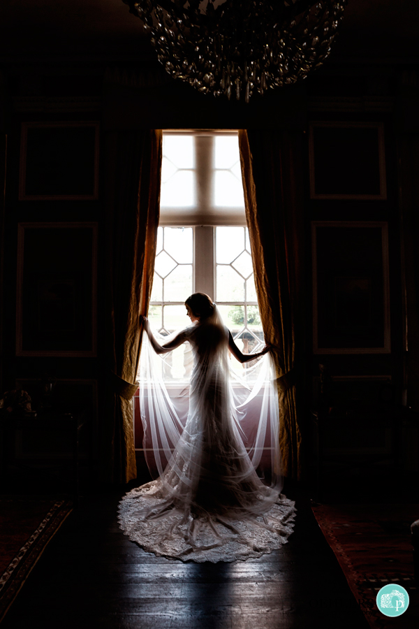 Silhouette of a bride posing against a window holding onto the curtains.