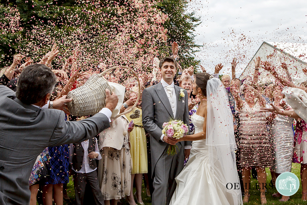 dad throws a basket of confetti over groom