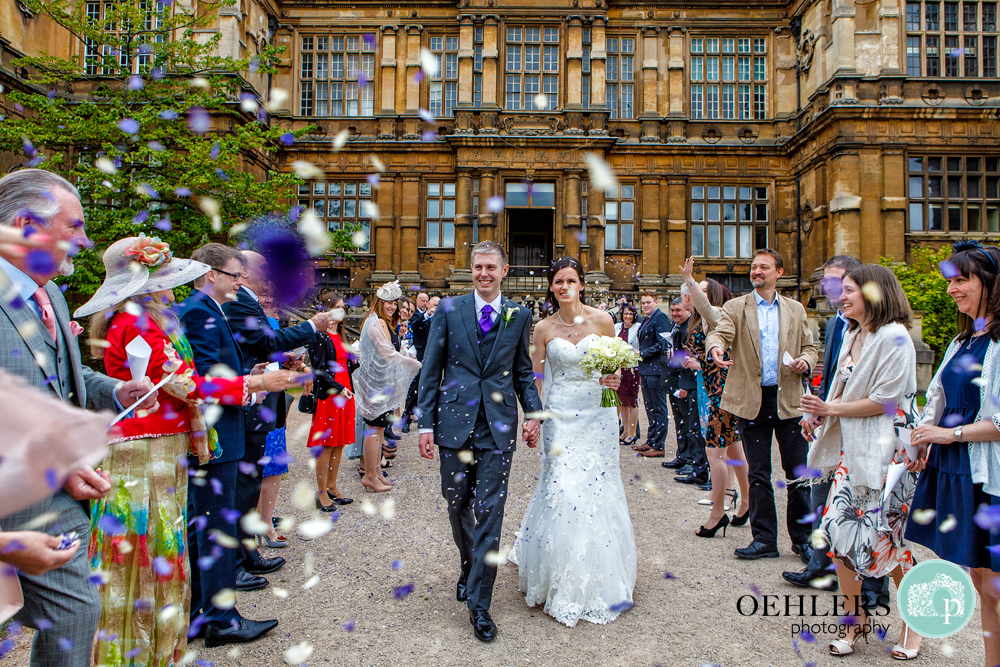 guests throwing confetti at Wollaton Hall