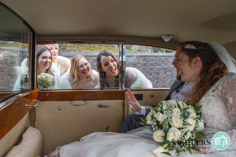 bridesmaids looking into car at bride