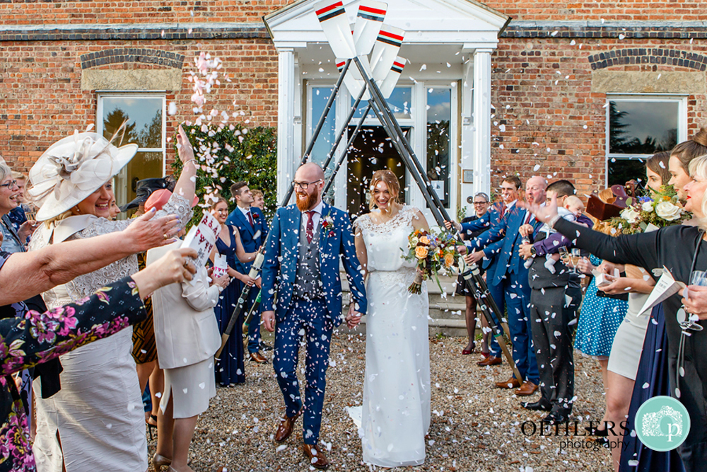 bride and groom walking through an arch of oars for their confetti shot