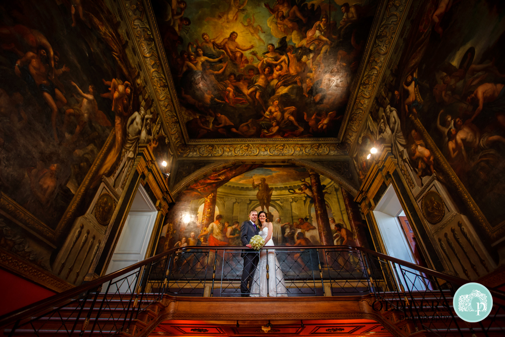 bride and groom standing on balcony with beautiful paintings as a backdrop