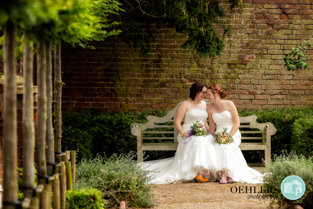 two brides sitting on a bench at the Walled Garden, Beeston