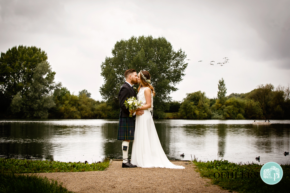 bride and groom kissing at a lake with bird flying in the sky
