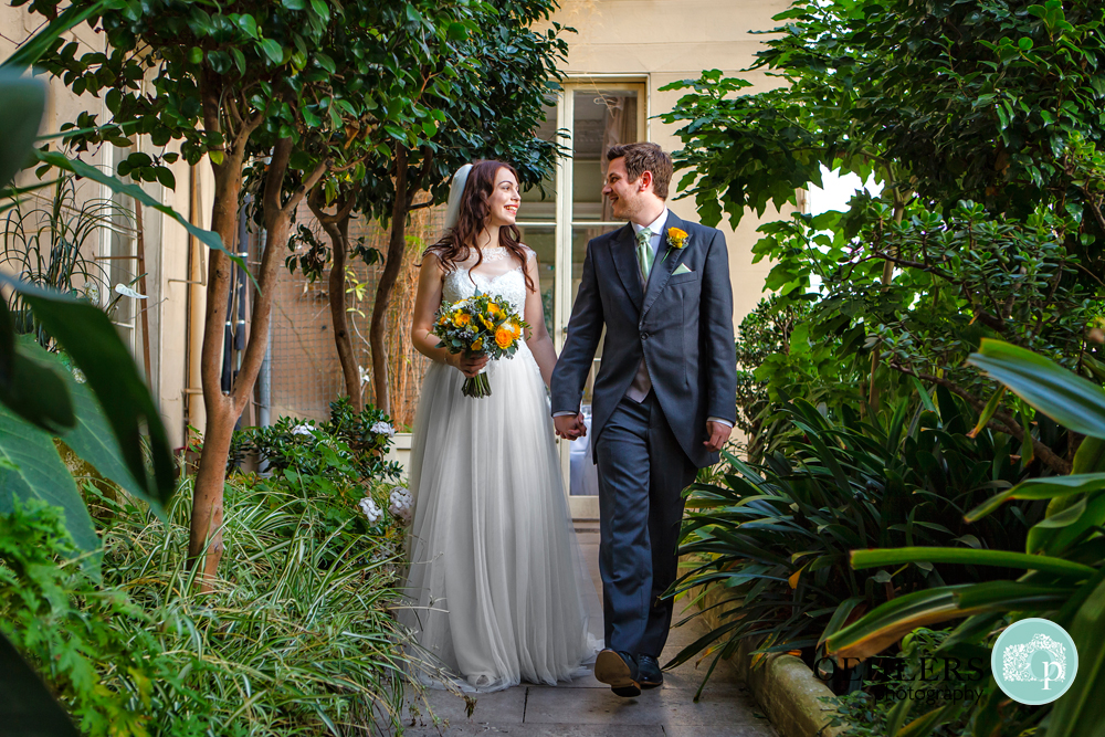 bride and groom walking in the conservatory at Prestwold
