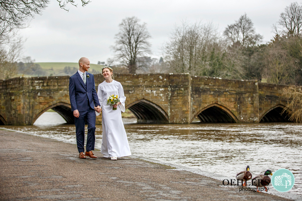 Bride and Groom walking along a river in Bakewell followed by ducks