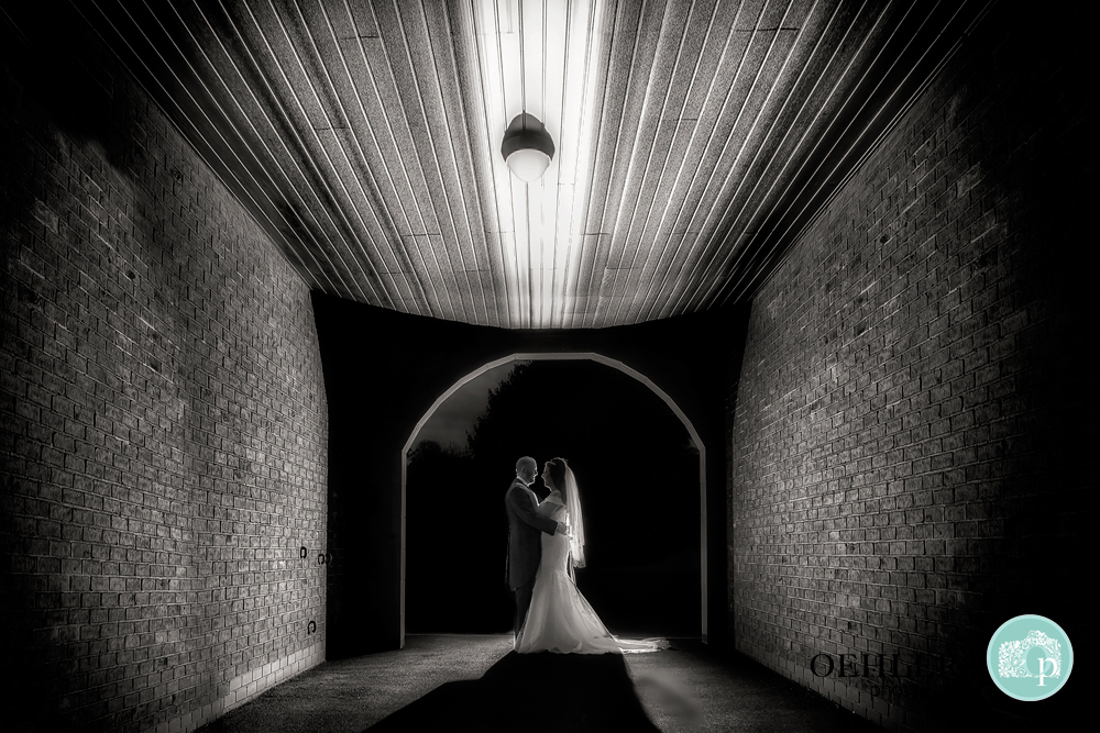 Black and White photo of Bride and Groom lit in an archway