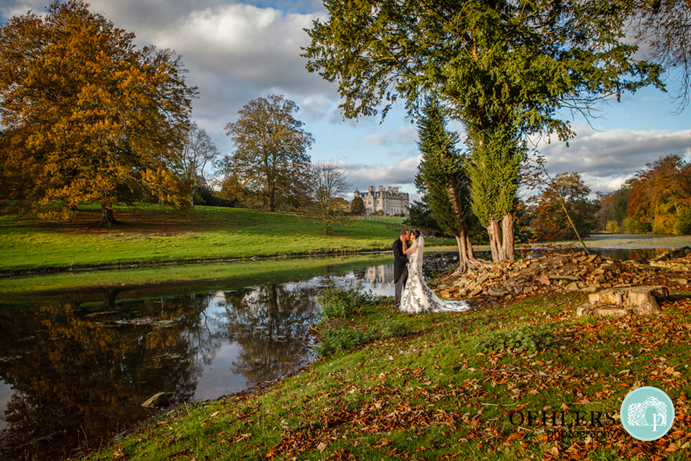 Bride and Groom by a lake with Stoke Rochford in the background