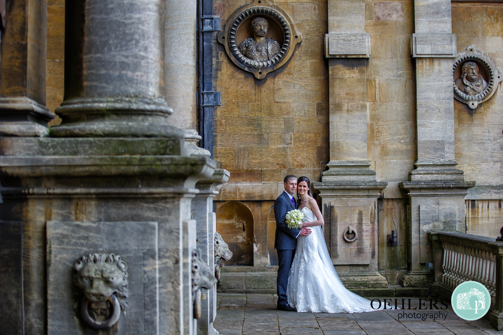 Bride and Groom pose in front of Wollaton Hall
