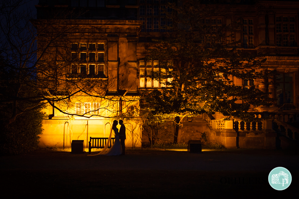 silhouette of Bride and Groom in front of a light at Wollaton Hall