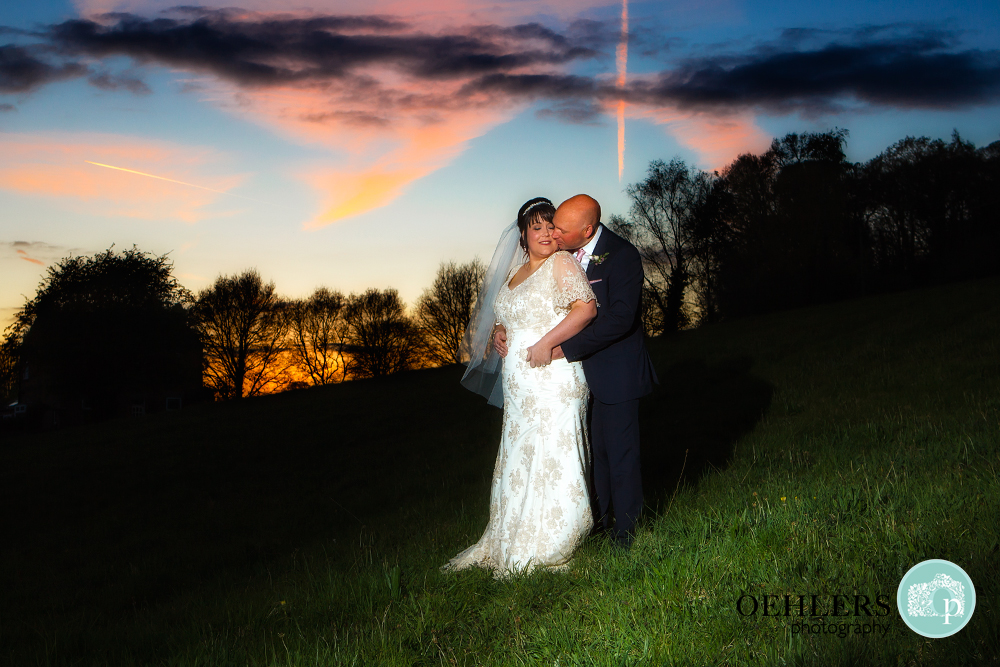 Bride and Groom cuddling with sunset in the background