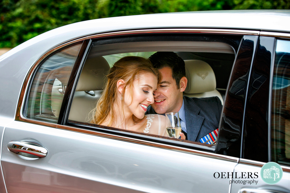 Groom snuggling up to Bride in the wedding car