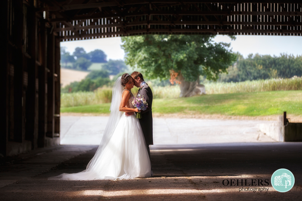 Bride and Groom cuddling in the barn at Shottle Hall