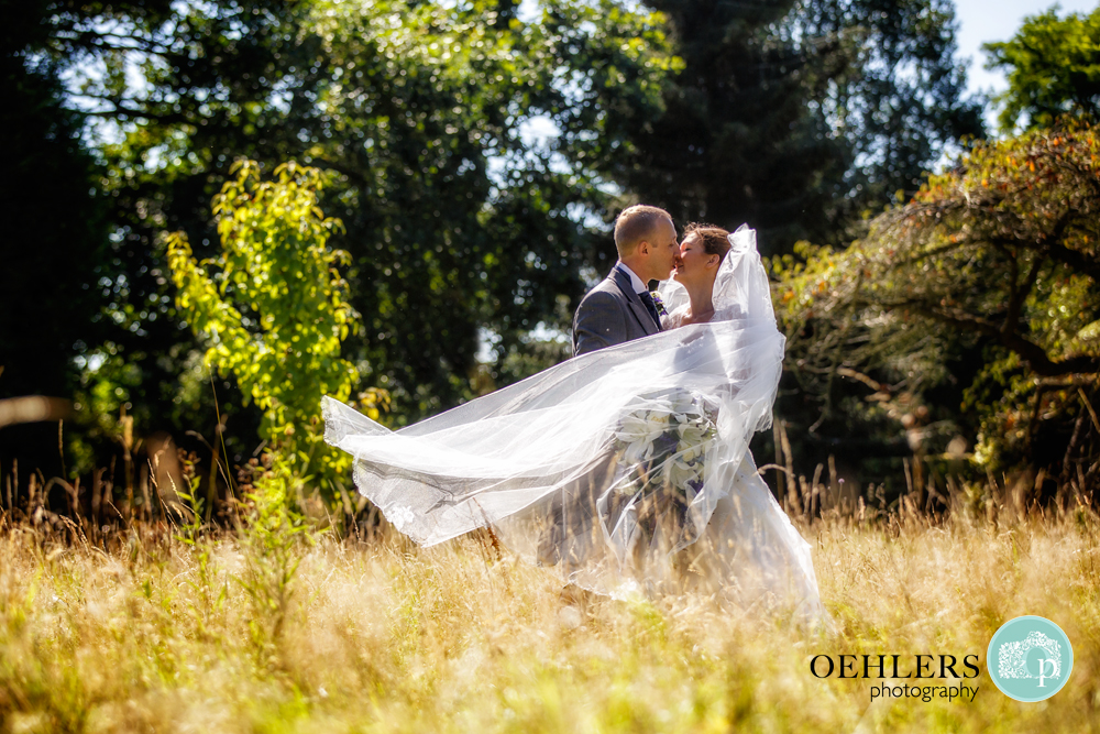 bride and groom kissing in a grassy field
