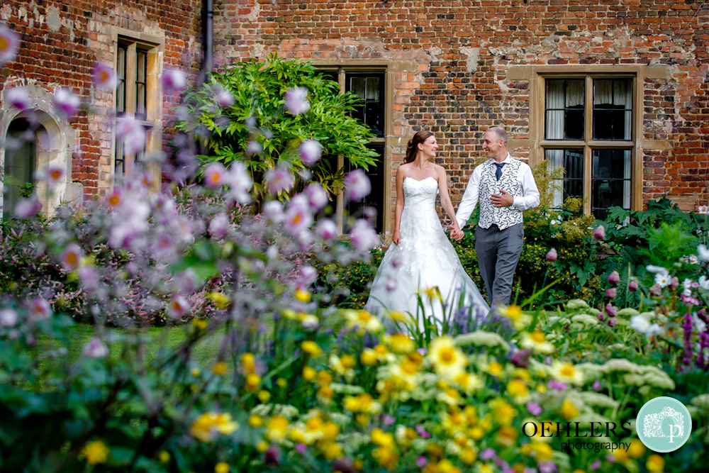 shoot through flowers at bride and groom walking