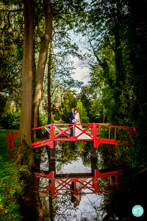 bride and groom posing on a red bridge
