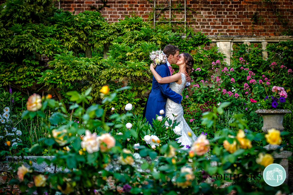 bride and groom kissing in the rose garden of Thrumpton Hall