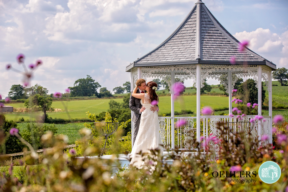Bride and Groom kissing in the gazebo at Shottle Hall