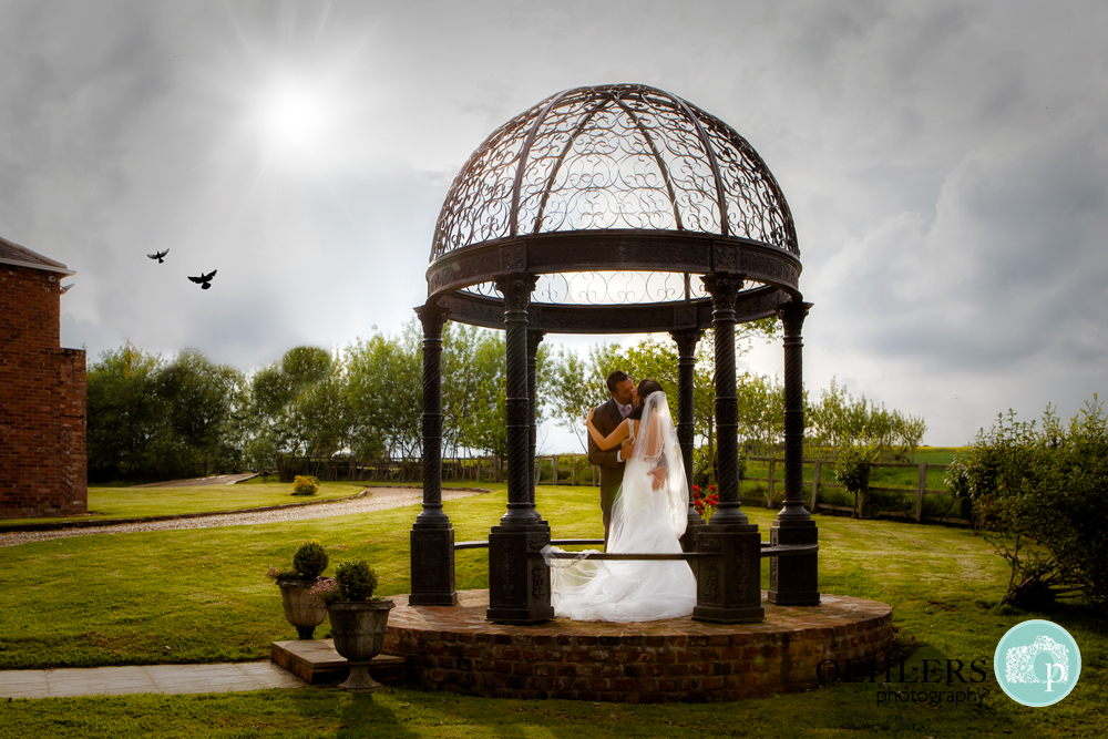 Bride and Groom kissing in the gazebo at Swancar Farm
