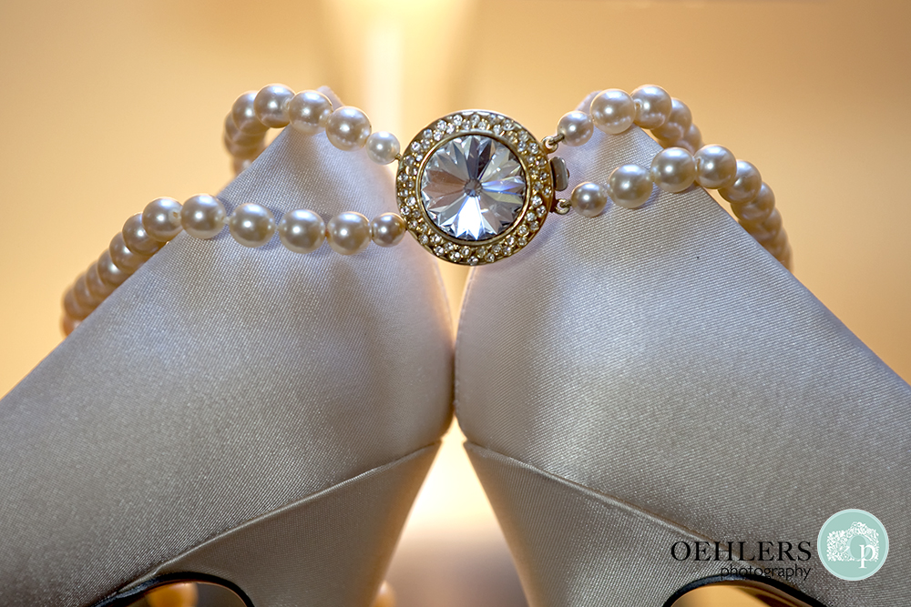 pearl bracelet hanging from wedding shoes