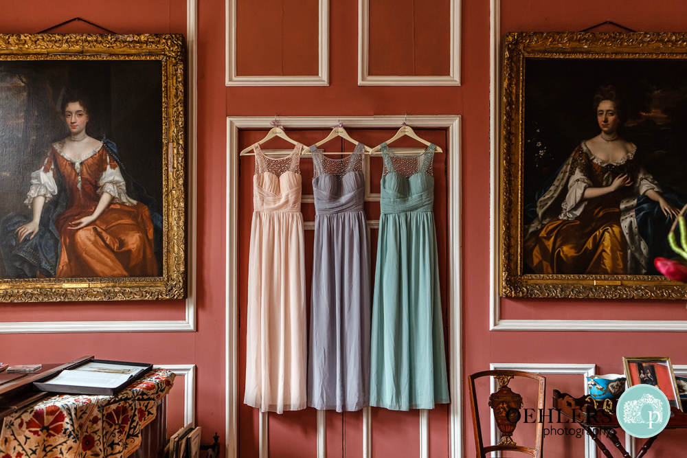 Three different coloured bridesmaids dresses hanging up