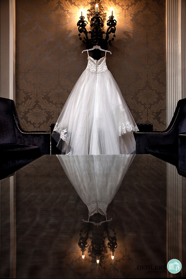 wedding dress hanging up with reflection