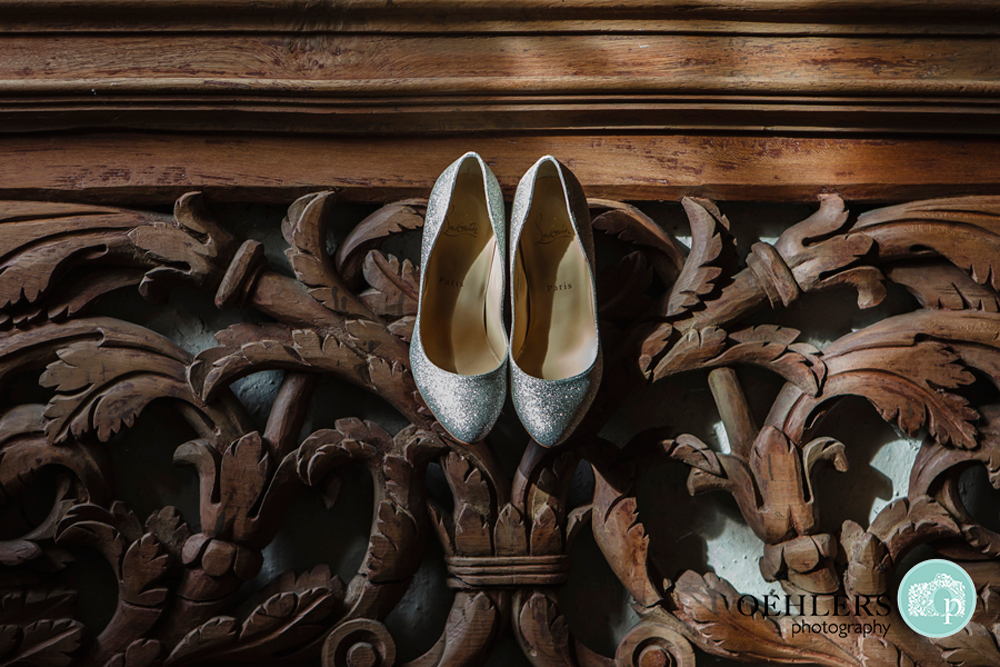 silver wedding shoes hanging from a wooden carved staircase