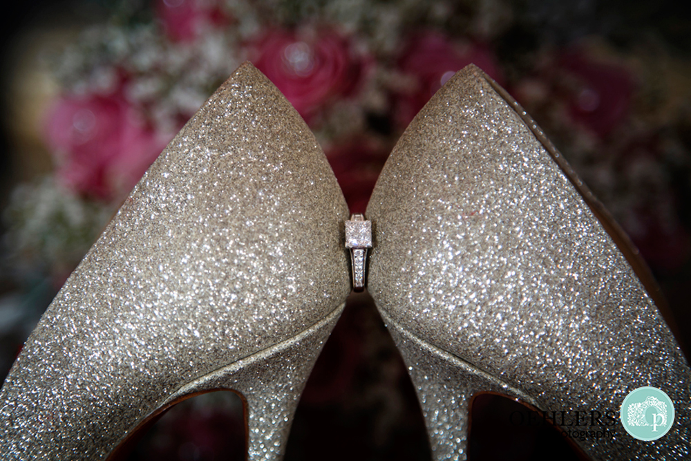 engagement ring in between backs of shoes
