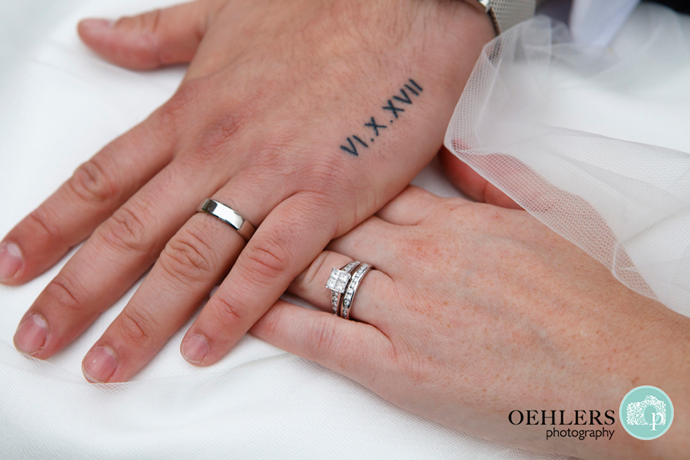 Groom and Bride's hands with rings and wedding date tatooed onto grooms hand