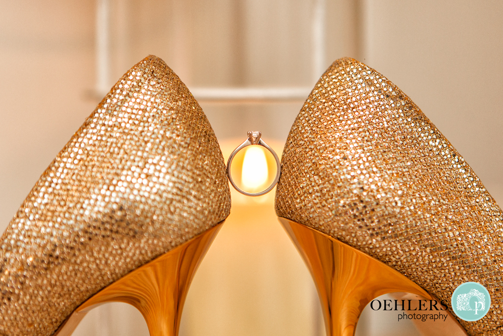 engagment ring perched in between wedding shoes lit by candle behind