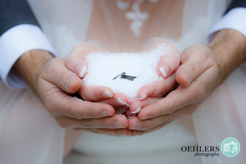 rings on snow held in groom's and bride's hands