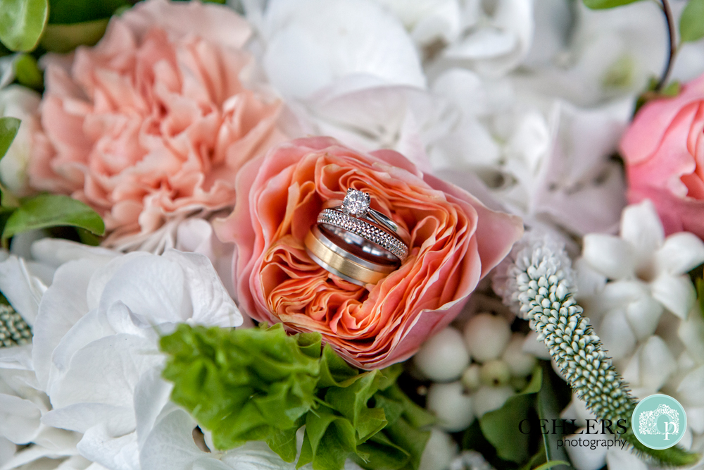 wedding rings and engagement ring balancing in a flower