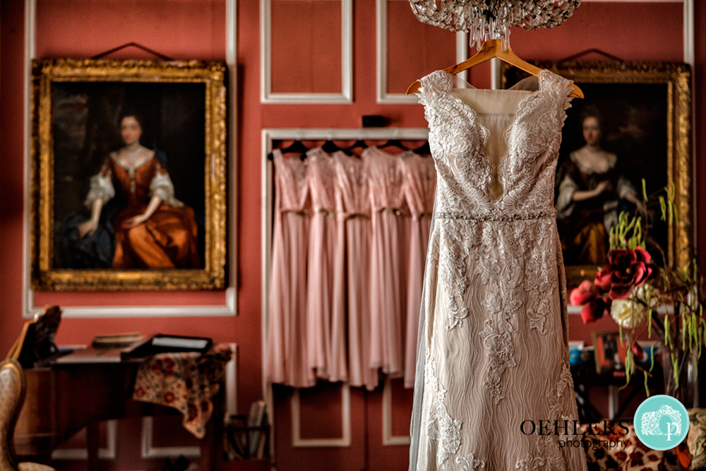 wedding dress hanging up in the pink room of Thrumpton Hall