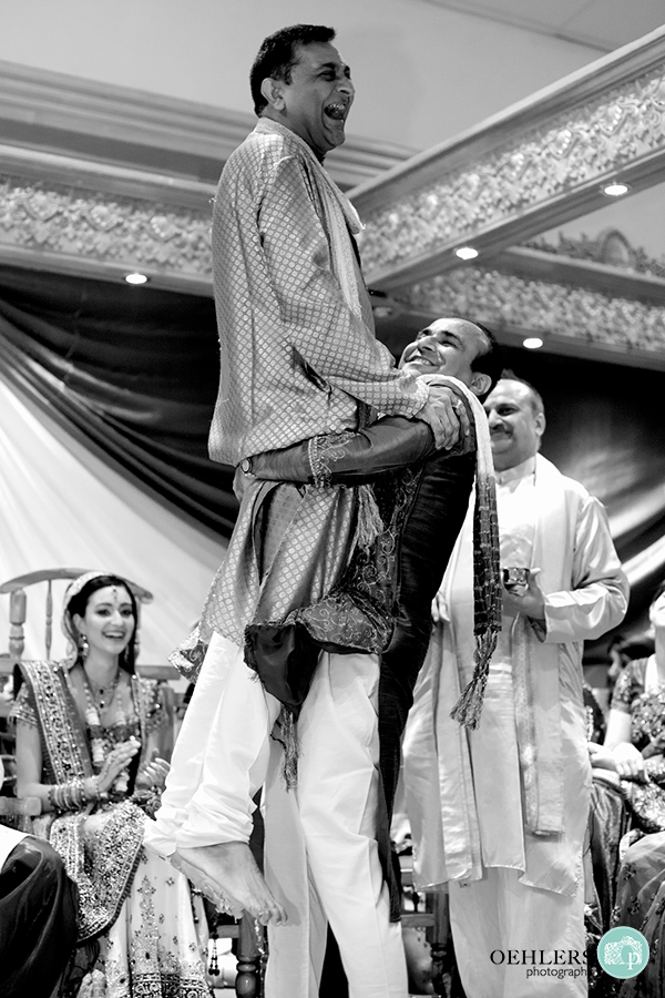 Indian wedding guests lifting father of the bride up