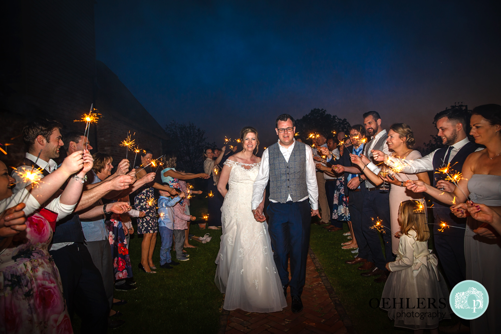 Front view of Bride and Groom walking through the tunnel of sparklers