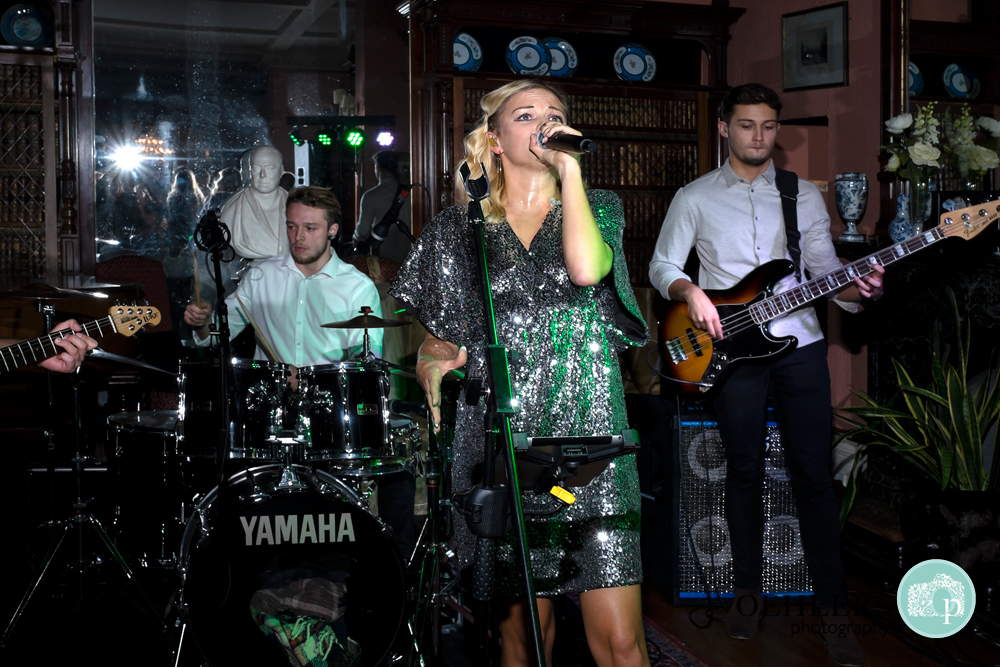 Lead singer with her band in the background entertaining the guests