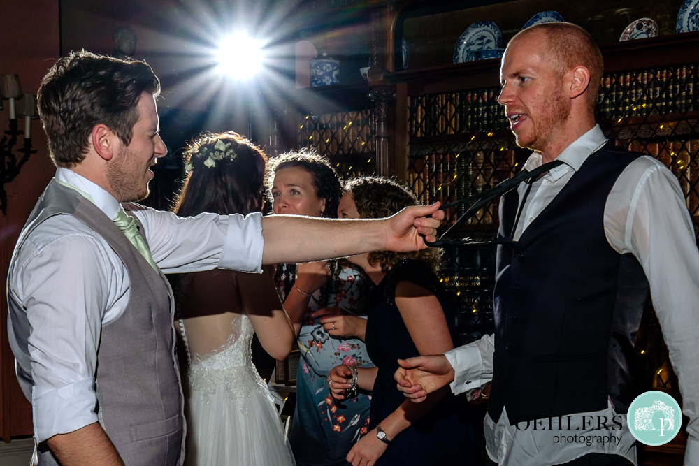 Groom pulling a guests tie whilst enjoying the party