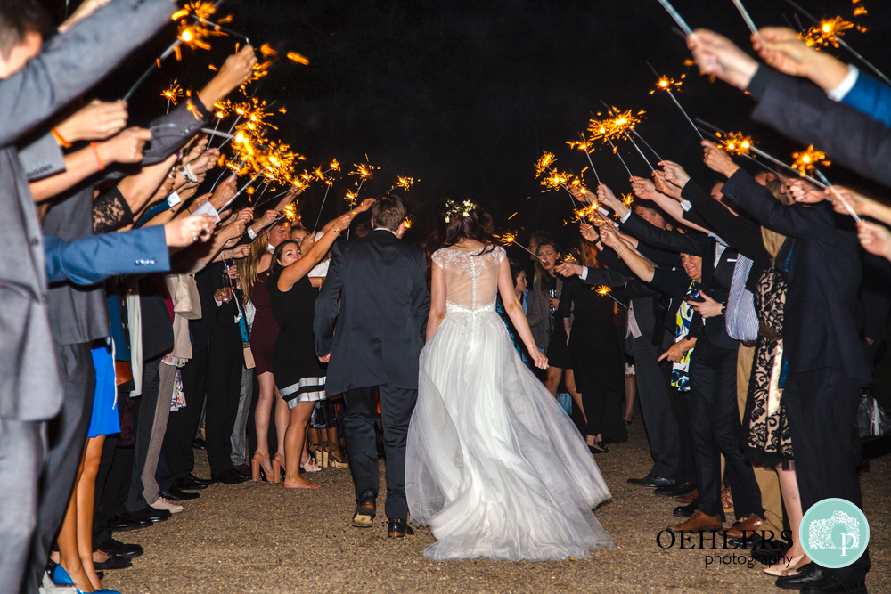 Guests form a sparkler tunnel as the Bride and Groom walk through it